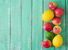 Ripe fruits (apples, lemons and limes) on a bright wooden background. Stock Images
