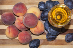 Ripe fruits and cidre. Peaches and plums with wine Stock Images