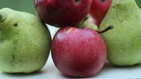 Ripe fruits: green pear, red apple and yellow cherry plum are lying on a white rural table against the background of a green garde stock video