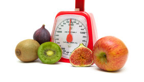 Ripe fruits and kitchen scales isolated close up on white backgr Royalty Free Stock Photography