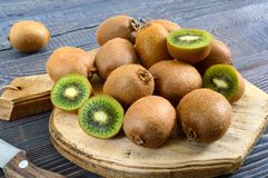 Ripe fruits of kiwi whole and halves are scattered on a cutting board. With an old knife on a wooden table stock image