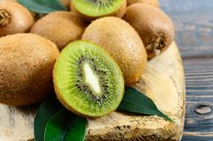 Ripe fruits of kiwi whole and halves are scattered on a cutting board. With an old knife on a wooden table royalty free stock photos