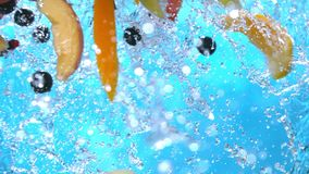 Ripe fruits peach slices orange black currant apple falling into water splash cascade in slow motion shot at 1500 fps