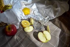 Free Ripe Fruits Red Apples, Cut Lemons On White Drapery With Folds, On Checkered Blanket With Glass And Apple Slices In Light Stock Photo - 198780460