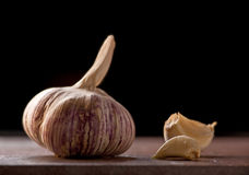 Ripe garlic head with a couple of peeled cloves. Side view of a piece of garlic with two cloves Stock Image