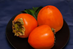 Ripe golden three persimmons on plate, dark background. These sweet and pulpy fruits can be eaten fresh, dried, raw, or. Sweet and pulpy of ripe golden three Royalty Free Stock Image