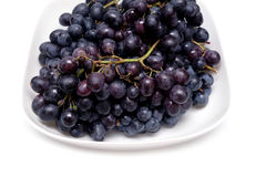 Ripe grape bunches in white bowl isolated Stock Photography