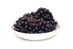 Ripe grape bunches in white bowl isolated Royalty Free Stock Images