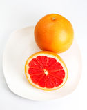 Ripe grapefruit with half on a plate over  white background clos Royalty Free Stock Photography