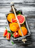 Ripe grapefruit in a wooden box. On wooden background stock photography