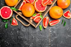 Ripe grapefruit on a wooden tray royalty free stock image