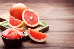 Ripe grapefruits slices. In bowl on brown wooden table stock photography