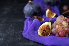 Ripe grapes and figs on dark wooden table Stock Photos