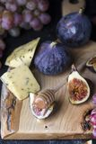 Ripe grapes and figs on dark wooden table Royalty Free Stock Images