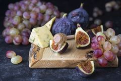 Ripe grapes and figs on dark wooden table Royalty Free Stock Image