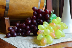 Ripe grapes and green grapes on wooden table. With wine barrel background Royalty Free Stock Photography