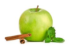 Ripe green apple with cinnamon sticks Royalty Free Stock Photos