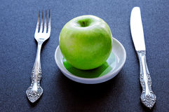 Ripe green apple. On a plate with a fork and knife Royalty Free Stock Photo