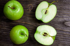 Ripe green apples and apple slices. On wooden gray background Stock Photos