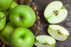 Ripe green apples and apple slices. On wooden gray background Royalty Free Stock Images