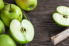 Ripe green apples and apple slices. On wooden gray background royalty free stock photography
