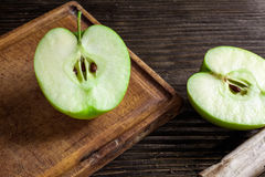Ripe green apples and apple slices. On wooden gray background royalty free stock photos