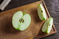 Ripe green apples and apple slices. On wooden gray background Royalty Free Stock Image