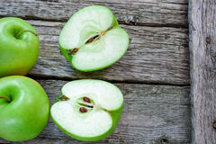 Ripe green apples and apple slices on wooden gray. Background stock images