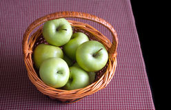 Ripe green apples in brown wicker basket on red tartan tablecloth  on black background Stock Photos