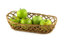 Ripe green apples in long brown wicker basket isolated Stock Photos