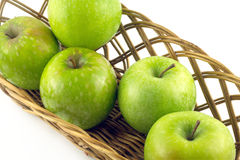 Ripe green apples in long brown wicker basket isolated Royalty Free Stock Photo