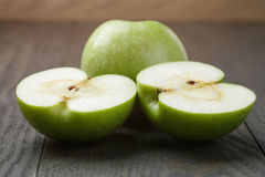 Ripe green apples sliced on wood table Royalty Free Stock Photography