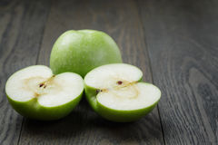 Ripe green apples sliced on wood table Stock Images