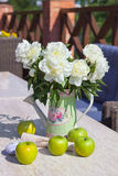 Ripe green apples and a vase of peonies on a marbl Royalty Free Stock Photography