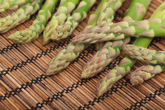 Ripe green asparagus on wooden mat Royalty Free Stock Image