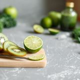 Ripe green fruits. Lime and kiwi on cutting board, close up. Copy space Stock Images