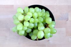 Ripe green grape berries in black round bowl top view Royalty Free Stock Images
