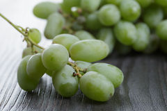 Ripe green grapes on black wood table Royalty Free Stock Photos