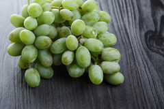 Ripe green grapes on black wood table Royalty Free Stock Images