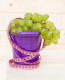Ripe green grapes in pail on wooden table Royalty Free Stock Photo