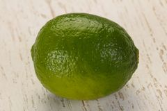 Ripe green lime. Over the wooden background stock images