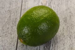 Ripe green lime. Over the wooden background stock photography