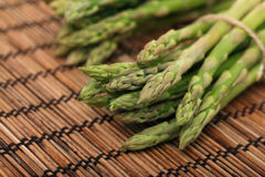 Ripe green mini asparagus on wooden mat Royalty Free Stock Images