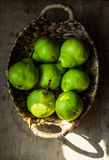 Ripe green organic pears in vintage wicker basket on weathered wood kitchen table, sunlight flecks Royalty Free Stock Photography