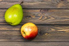Ripe pear and apple. Ripe green pear and red-yellow Apple on a wooden table. Top view. Rustic style Royalty Free Stock Images
