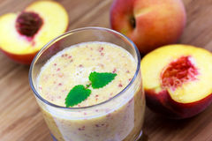 Ripe half of peach, smoothie of peach, on wooden b Stock Photo