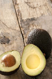 Ripe halved avocado pear on a rustic table Stock Photos