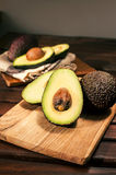 Ripe halved avocado on wooden cutting board Royalty Free Stock Image