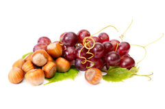 Ripe hazelnuts and juicy grapes on a white. Royalty Free Stock Photography