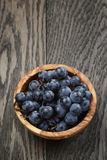 Ripe isabella grapes in wood bowl on table Stock Photo